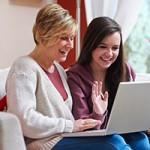 mother showing daughter computer